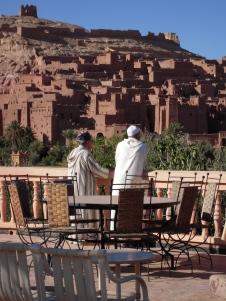 Men contemplate Kasbah of Ait Benhaddou